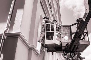 Restauratorin auf Hebebühne setzt eine Skulptur in eine Fassaden ein
